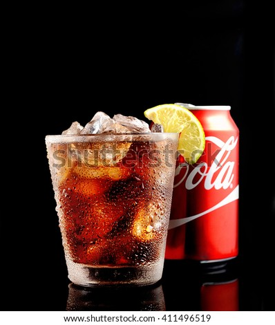 POLTAVA, UKRAINE, FEBRUARY 19, 2016 Can and glass of Coca-Cola with ice on black  background. Coca is a carbonated soft drink sold in stores, restaurants, and vending machines throughout the world.