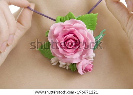 polymer clay jewelery: woman with a rose necklace around her neck, close-up