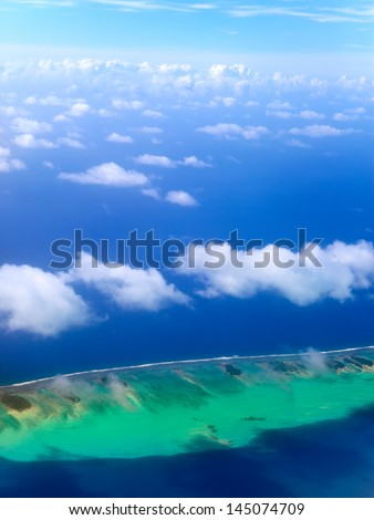 Polynesia. The atoll in ocean through clouds. Aerial view.  - stock photo