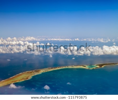 Polynesia. The atoll ring in ocean is visible through clouds. Aerial view. - stock photo