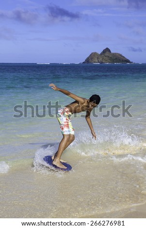 polynesian boy riding his skim board in Hawaii - stock photo