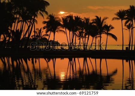 Polynesian idyll: silhouettes of beachgoers and palm trees shortly before sunset at Anaehoomalu Bay on the Kona Coast of the Big Island - stock photo