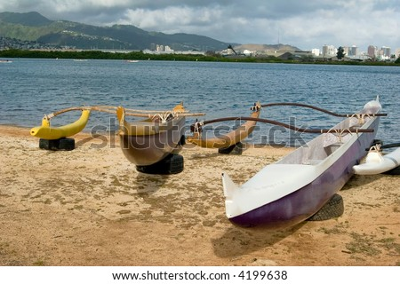 Polynesian outrigger canoes sitting on the sea shore
