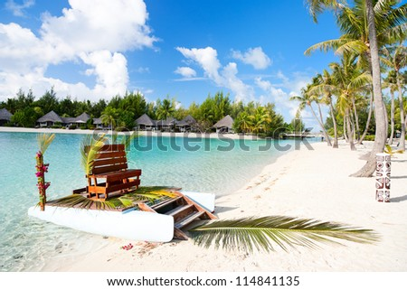 Polynesian wedding boat with chair at exotic beach - stock photo