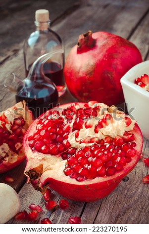 Pomegranate and bottles of essence or tincture on wooden table - stock photo