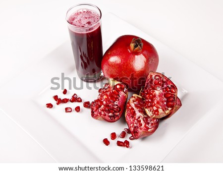 Pomegranate and juice in glass on white background - stock photo