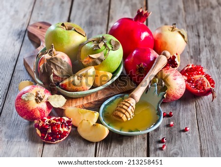 Pomegranate, apple and honey, traditional food of jewish New Year celebration, Rosh Hashana. Selective focus. - stock photo