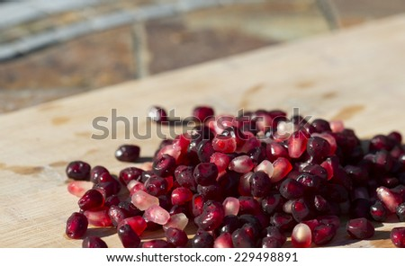 pomegranate arils (seeds) in a pile with blurred table background - stock photo