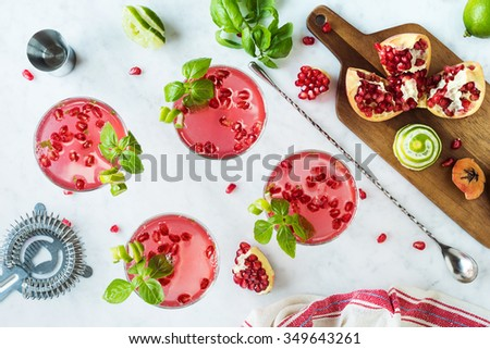 Pomegranate Basil Martinis or Gin Smash Cocktails on the Bar Counter with Ingredients - stock photo