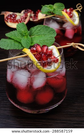 pomegranate drink with ice, a slice of lemon and mint - stock photo