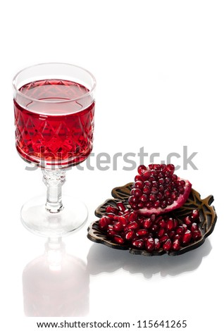 Pomegranate juice and pomegranate seeds on a white background