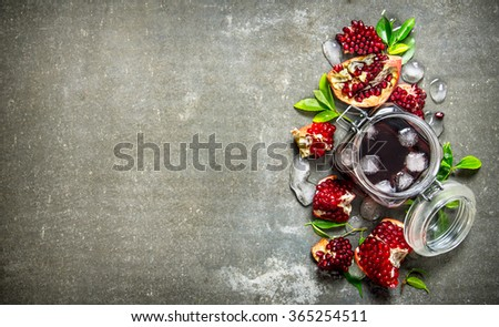 Pomegranate juice in a tin with ice and slices with leaves . On the stone table. Free space for text . Top view - stock photo