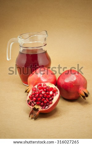 Pomegranate juice on brown wooden background