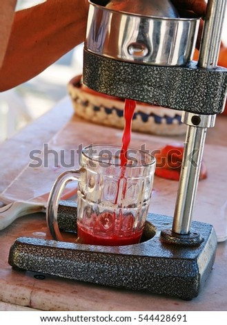 pomegranate juice prepared in street with old metal juice press squeeze machine