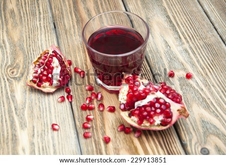 Pomegranate juice with fruit on the wood background - stock photo