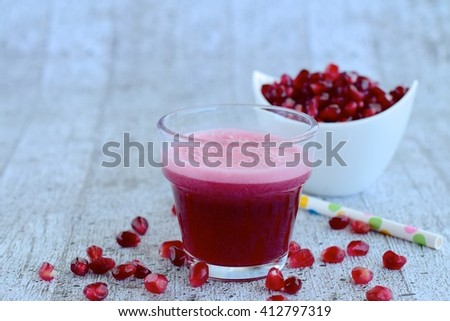 Pomegranate juice with pomegranate seeds on grey background - stock photo