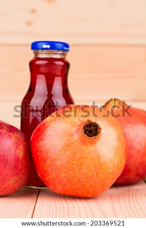 pomegranate juice with pomegranates on the wooden background closeup - stock photo