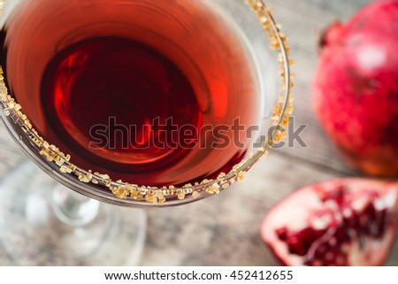 Pomegranate margarita cocktail on rustic wooden background
