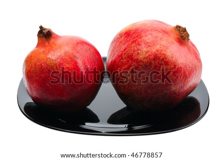Pomegranate on a black platte on white background, isolated.