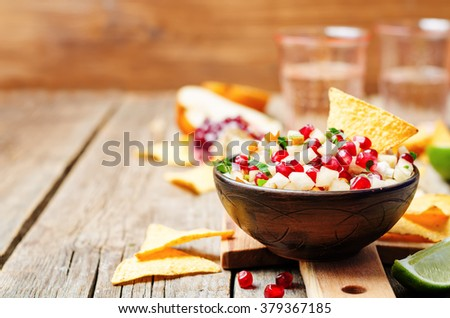 pomegranate pear salsa on a dark wood background. toning. selective focus - stock photo