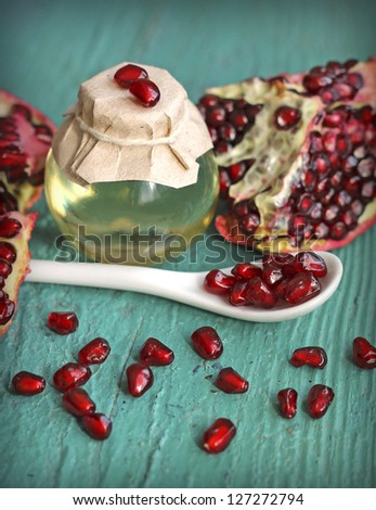 Pomegranate seed oil in bottle on blue wooden background, close-up
