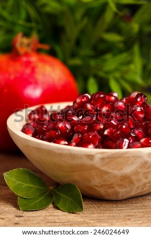 Pomegranate seeds in wooden plate with fruit and leaves in the back - stock photo