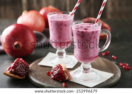 Pomegranate smoothie in glass on black background - stock photo