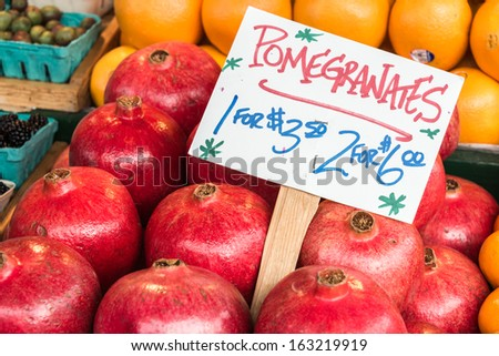 Pomegranates for sale. Sign identifying fruit and price. - stock photo