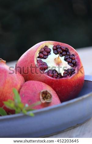Pomegranates on Blue Pottery Dish 3 - stock photo