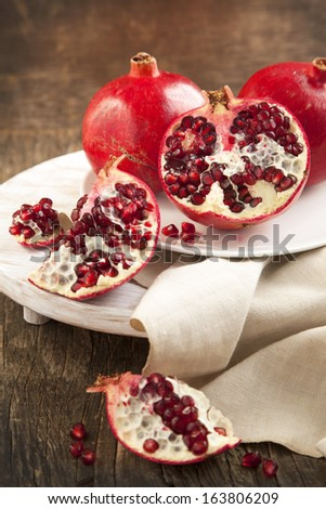Pomegranates over Wooden Background.