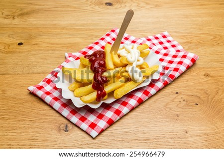 pommes fries with ketchup and mayo sauce on a tablecloth - stock photo