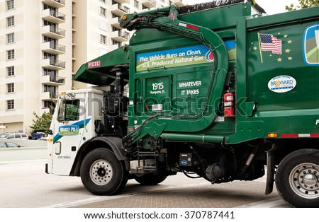 POMPANO BEACH, FL - JANUARY 8: Natural gas powered garbage truck adorned with various signs photographed on Jan. 8, 2016 in Pompano Beach, Florida