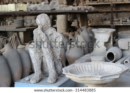 POMPEII, ITALY, JUNE 26, 2015: Ancient artifacts along with a human casing found in the ruins of the old city of Pompeii, Italy - stock photo