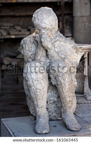 POMPEII -SEPTEMBER 19. Plaster cast of one of the victims covered in ash on September 19, 2012 in Pompeii, Italy. The eruption of 79 AD buried the city preserving details of the life in a Roman city - stock photo