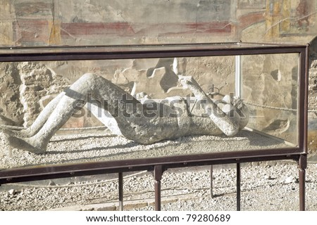 Pompeii was destroyed by the eruption of Mt. Vesuvius during 2 days in 79AD. This is a plaster cast of one of the victims displayed to the public on site in a glass case. - stock photo