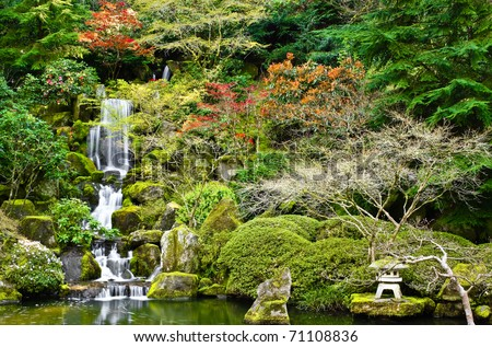 Pond and stone tea lights in a Japanese garden. - stock photo