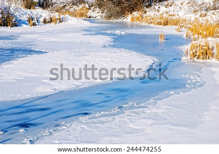 Pond covered in snow and ice - stock photo