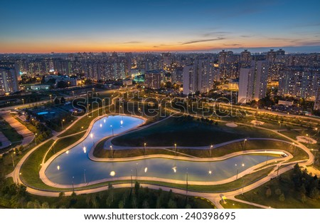 Pond in Dusseldorf park near the illuminated district of Moscow at evening.  - stock photo