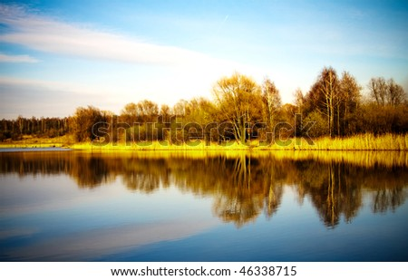 Pond water surface with reflection of colorful trees in autumn park - stock photo