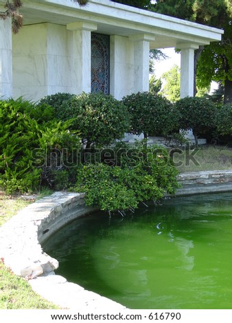 Pond with building aside it. - stock photo