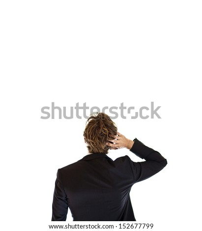 Pondering businessman looking at wall - stock photo
