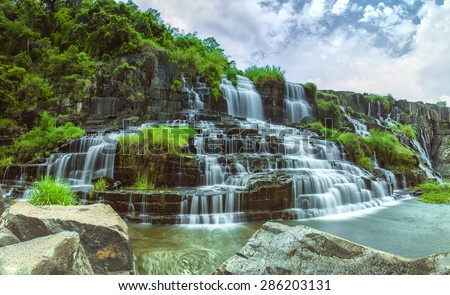 Pong our on summer days with many storied stone structure water flowing in the great stone steps. First waterfall in Lam Dong is here - stock photo