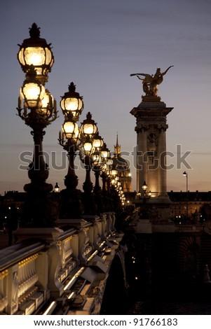 Pont Alexandre III Bridge illuminated at night in Paris, France - stock photo