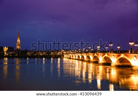 Pont de Pierre stone bridge on the river garonne in Bordeaux, France at night with the st michel church in the background