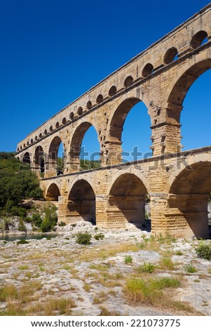 Pont du Gard is an old Roman aqueduct near Nimes in Southern France, bridge over river Garde on sunny day wit blue sky, - stock photo