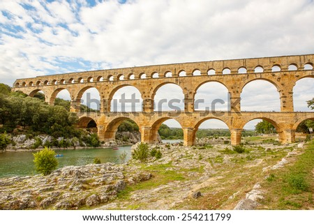Pont du Gard is an old Roman aqueduct near Nimes in Southern France. Travel destination for tourists in Provence. - stock photo