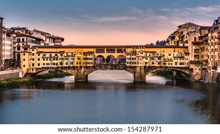 Ponte Vecchio at sunset in Florence, Italy. The bridge spans the Arno river at its narrowest point.