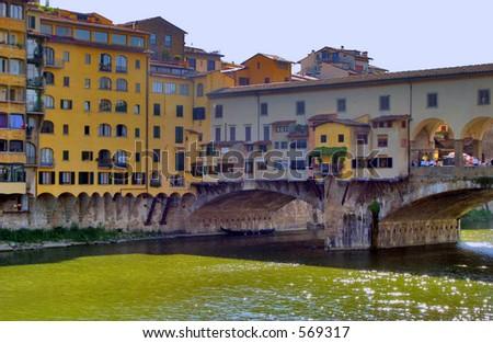 Ponte Vecchio bridge and the glistening green Arno River - stock photo