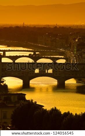 "Ponte Vecchio - the bridge-market in the center of Florence.Italy. Ponte Vecchio - the ""Old Bridge"" is accompanied by neighbouring bridges behind it: Ponte Santa Trinita and the Ponte alla Carraia. - stock photo"