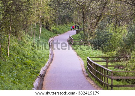PONTEVEDRA, SPAIN - APRIL 5, 2015: A group of people play sports, walking or running along a path near the river. - stock photo